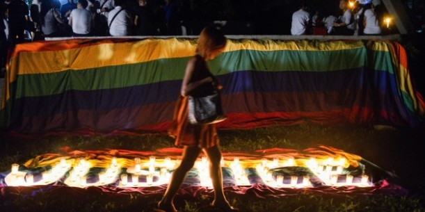A transgender Filipino walks across the lit candles formed ""